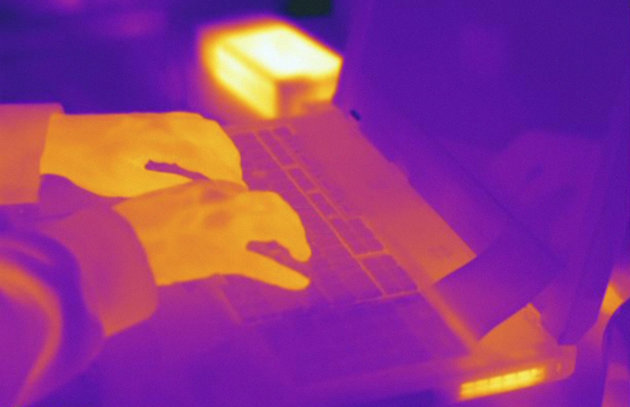 Thermogram of hands typing on a laptop computer. The temperature scale runs from white (warmest) through yellow, orange, red, purple and black (coldest).