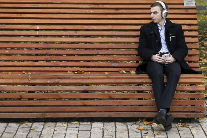 A man listens to music while sitting on a bench at a park near a pigeon, in central Kiev, Ukraine, October 22, 2015. REUTERS/Valentyn Ogirenko - RTS5PQP