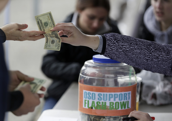 "People donate money during a flash football game organized by Arlington High School football player Max Gray, 18, to raise money for Jonielle Spiller, the mother of youth football player Jovon ""Jo Jo"" Mangual, 13, who died during the Oso mudslide, in Arlington, Washington April 4, 2014. About 30 people have been confirmed dead from the slide, which roared over the north fork of the Stillaguamish River and state Highway 530, engulfing about three dozen homes on the outskirts of the rural town of Oso in the foothills of the Cascade Mountains. Another 17 remain listed as missing.  REUTERS/Jason Redmond (UNITED STATES - Tags: DISASTER ENVIRONMENT SOCIETY SPORT) - RTR3K0DW"