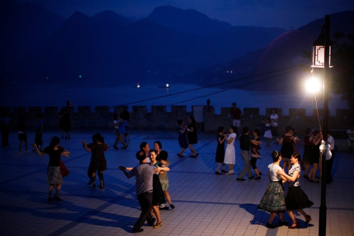 Local residents dance at a square next to the Yangtze River in Badong, Hubei province August 8, 2012. REUTERS/Carlos Barria (CHINA - Tags: SOCIETY) - RTR36FZ4