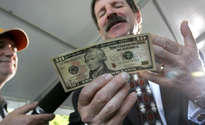 """Thomas Ferguson, Director for the Bureau of Engraving and Printing, holds a new $10 note during an interview after its unveiling on Ellis Island, New York, Wednesday Sept. 28, 2005. The most noticeable difference in the newly designed bill is the addition of subtle background colors of orange, yellow and red. Additionally, the words """"We The People"""" is printed in red next to the portrait of first Treasury Secretary Alexander Hamilton. The note is expected to go into circulation in early 2006. (AP Photo/Bebeto Matthews)"""